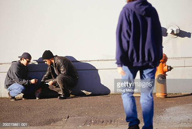 Two teenage boys (16-17) rolling joint by wall
