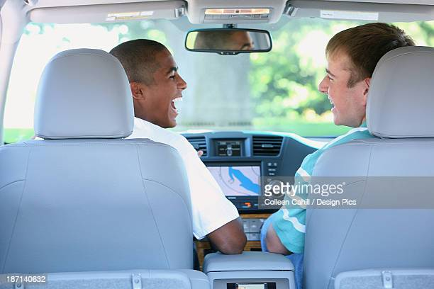 Two Teenage Boys Sitting And Laughing In The Front Seat Of A Car