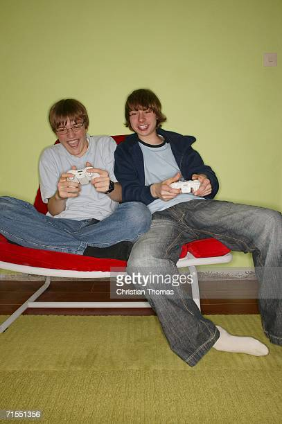 Two teenage boys sitting on chair playing computer game