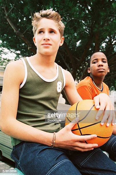 Two teenage boys (14-16) sitting outdoors with a basketball
