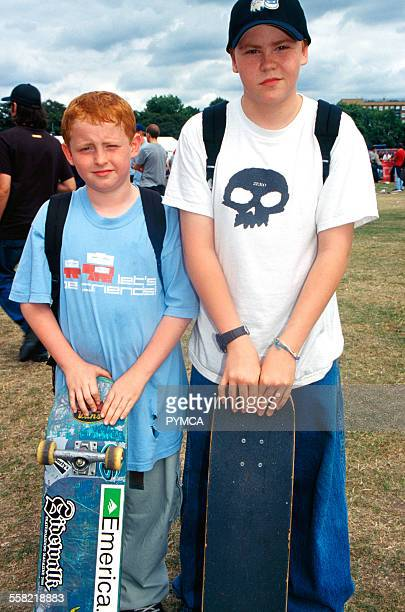 Two teenage boys standing with their skateboards at Urban Games/Board X Clapham Common London UK 1990s