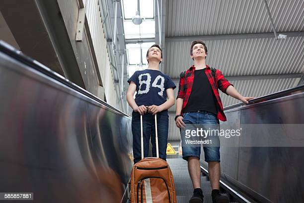 Two teenage boys with baggage standing on an escalator