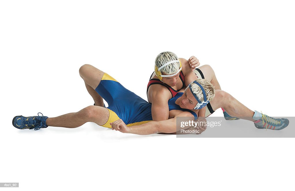 two teenage caucasian male wrestlers from opposing teams stuggle on the mat and the one in red tries to pin the one in blue