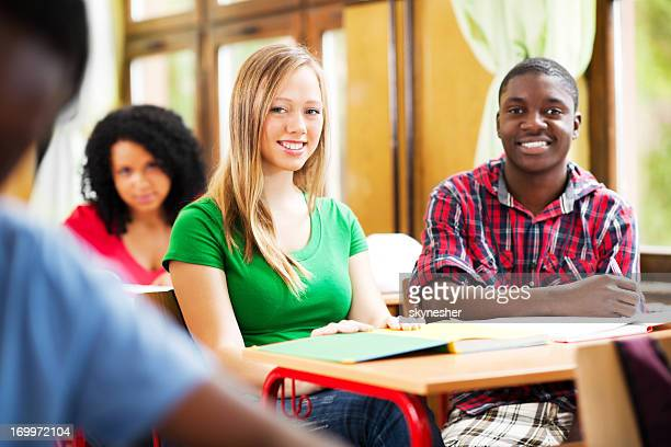 Deux jeunes camarades de classe assis et regardant la caméra.