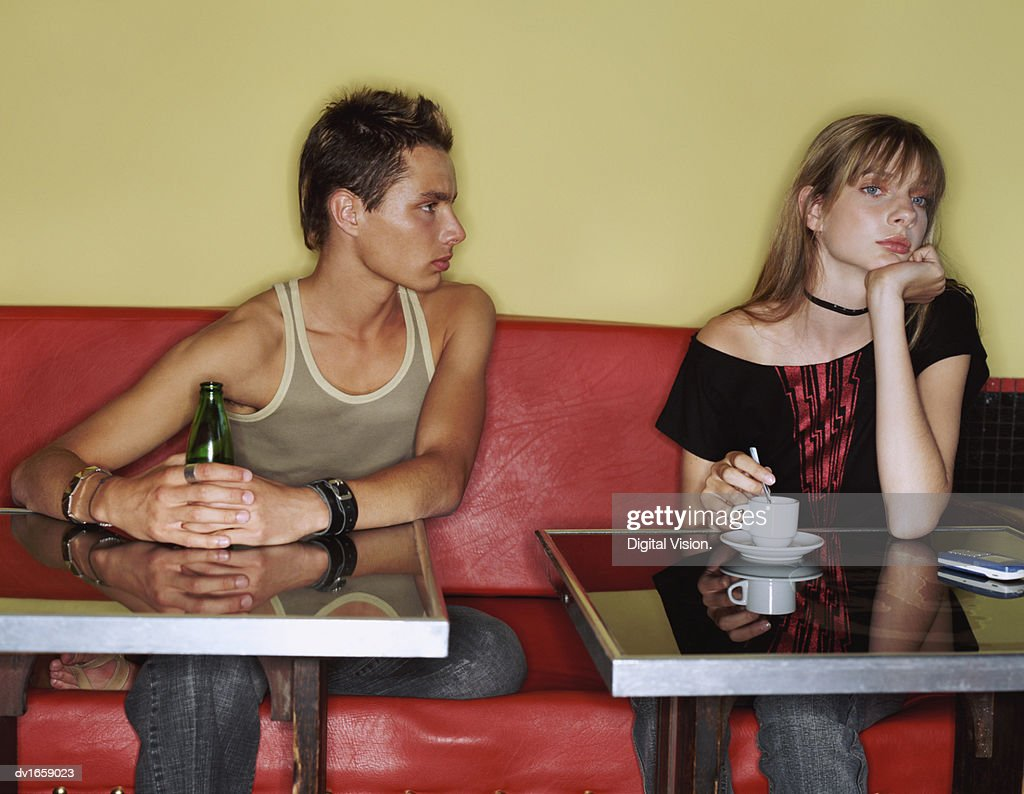 Two Teenage Friends Sit Side-by-Side in a Cafe, Girl Ignoring the Staring Boy : Stock Photo