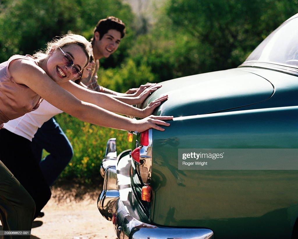Two teenage girls and teenage boy (15-19) pushing car, portrait : Stock Photo
