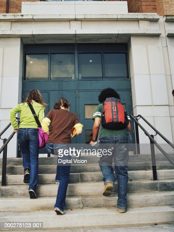 Two teenage girls and teenage boy (14-16) walking up school steps, rear view