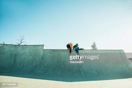 Two teenage girls climbing in skatepark