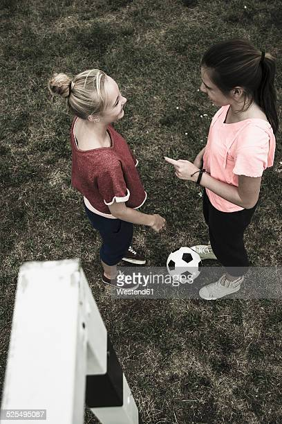Two teenage girls communicating on a football ground, elevated view