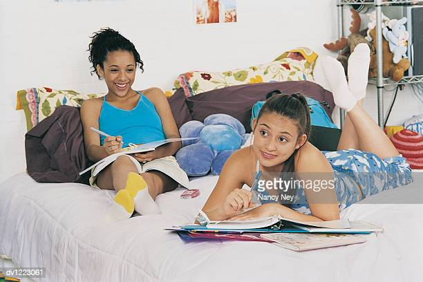 Two Teenage Girls Daydreaming and Writing in Folders, Lying on a Bed in a Bedroom