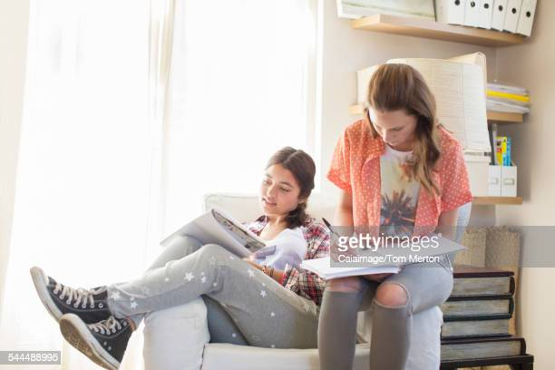 Two teenage girls doing homework in room