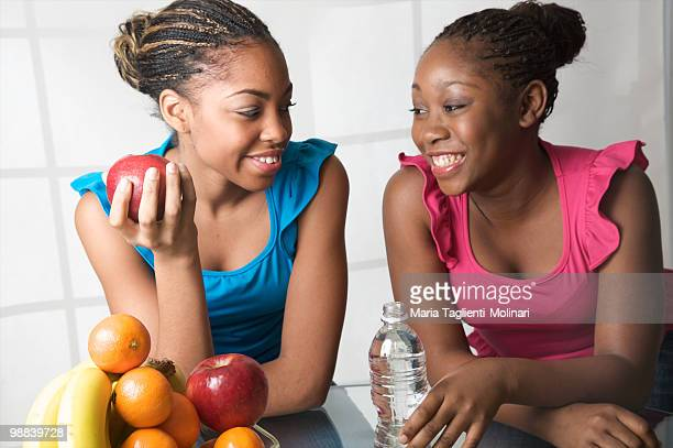 Two teenage girls eating apple and drinking water