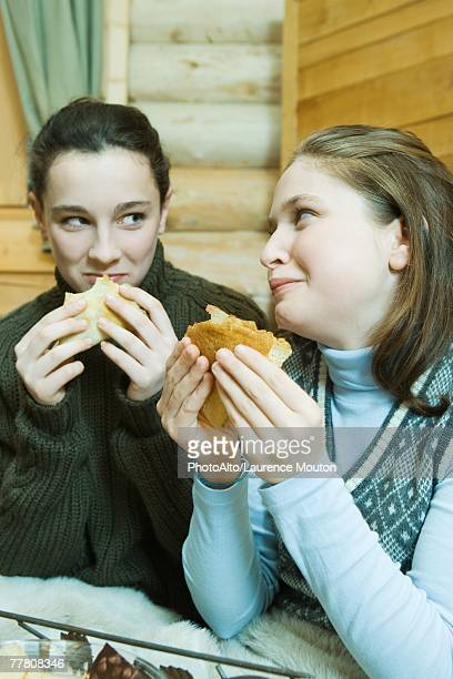 Two teenage girls eating crepes, looking at each other