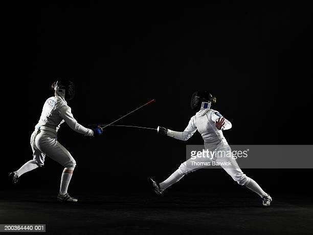 Two teenage girls (15-18) fencing, side view