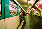 Two teenage girls (17-19) getting on train in Metro, Paris, France