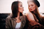 Two teenage girls having fun on beach pulling faces