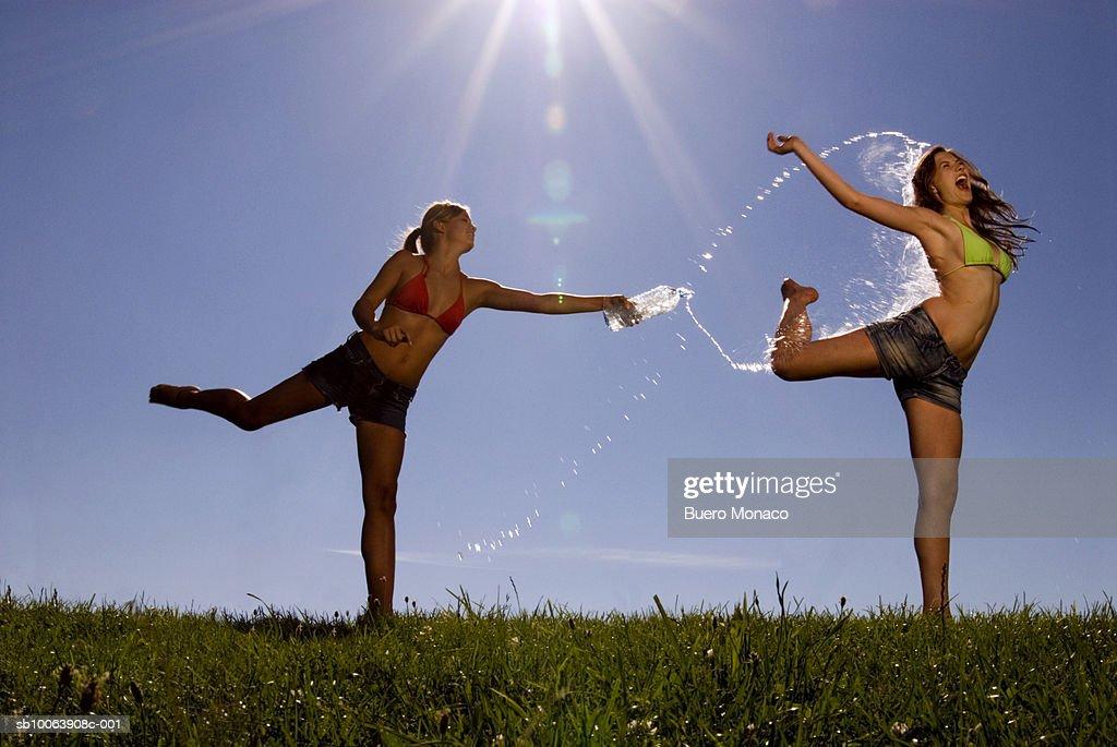 Two teenage girls (16-18) having water fight : Stock Photo