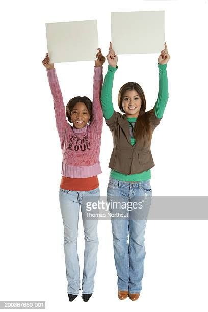 Two teenage girls (15-17) holding blank signs above heads, portrait