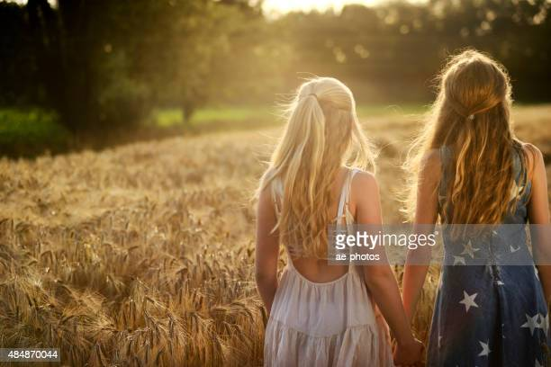 Two teenage girls holding hands in a barley field