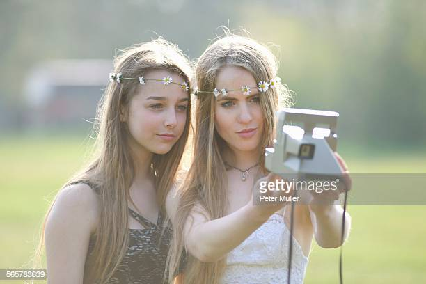 Two teenage girls in park taking instant camera selfie