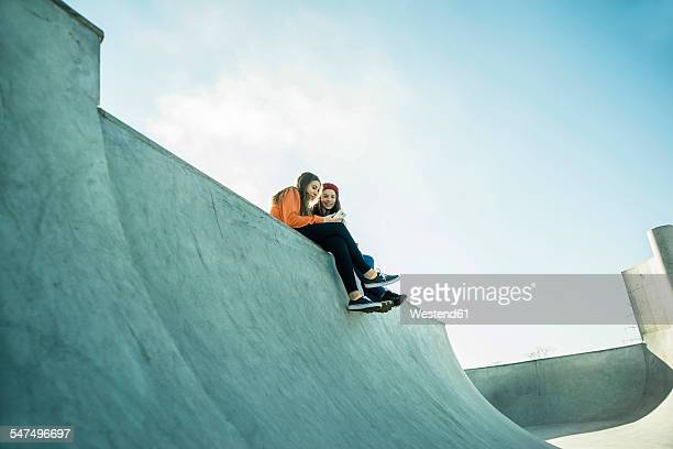 Two teenage girls in skatepark sharing cell phone