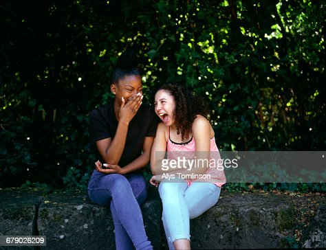 Two teenage girls laughing together in a park : Stock Photo