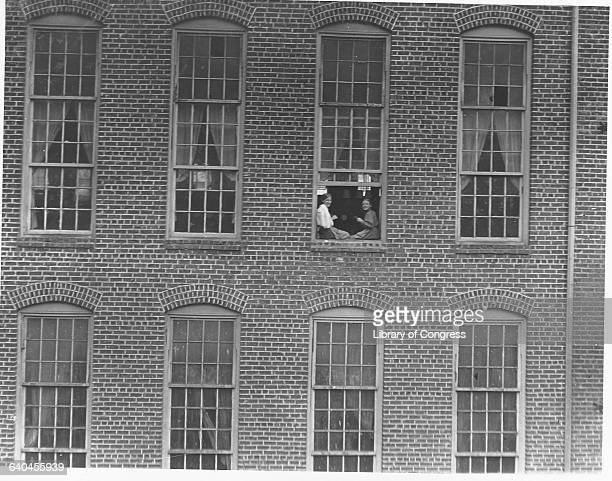 Two teenage girls on a break sit together in the window of the factory where they work South Carolina 1908   Location High Shoals North Carolina USA