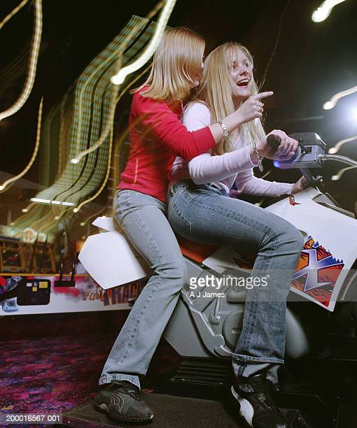 Two teenage girls (15-18) on scooter at video game arcade