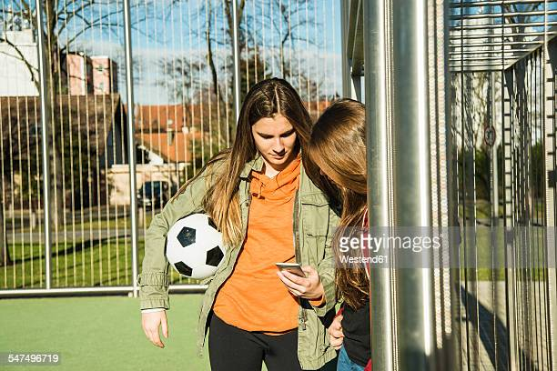 Two teenage girls on sports ground sharing cell phone