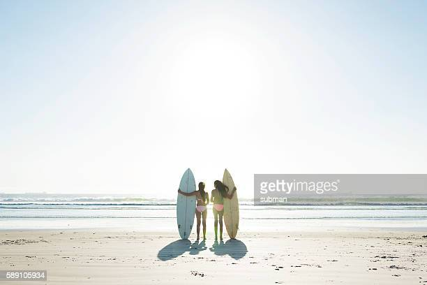 Two Teenage Girls On The Beach Holding Their Surfboards