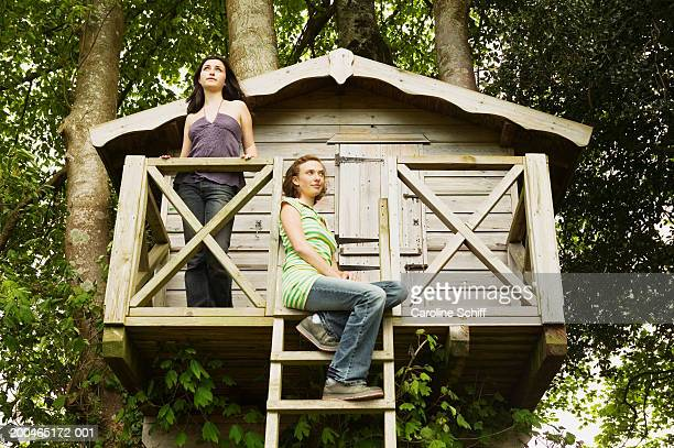 Two teenage girls on tree house, low angle view
