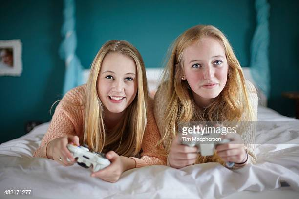 Two teenage girls playing on computer game in bedroom