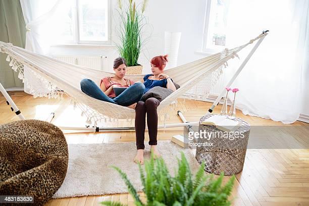 Zwei weibliche Teenager entspannen in der Hängematte und Nutzung tablet pc