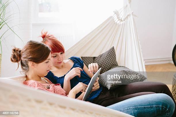 Zwei weibliche Teenager entspannen in der Hängematte, Lesung tablet pc