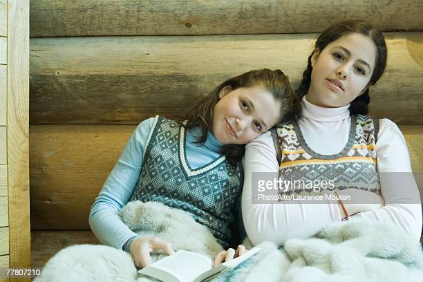 Two teenage girls sharing blanket, smiling at camera, one holding book, resting head on the other's shoulder