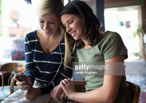 Two teenage girls sharing earphones in coffee house