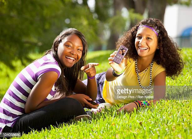 Two Teenage Girls Showing A Picture Of Themselves On A Cell Phone