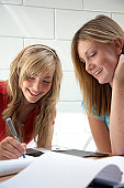 Two teenage girls (14-16) sitting at desk,one writing in exercise book