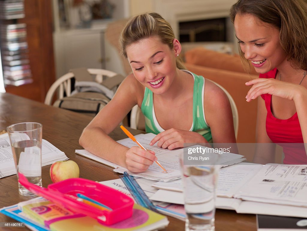 Two teenage girls sitting at table studying and smiling : Stock Photo