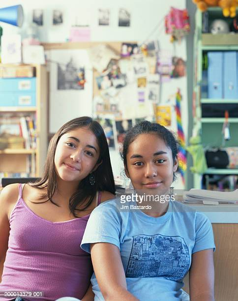 Two teenage girls (12-14) sitting in classroom