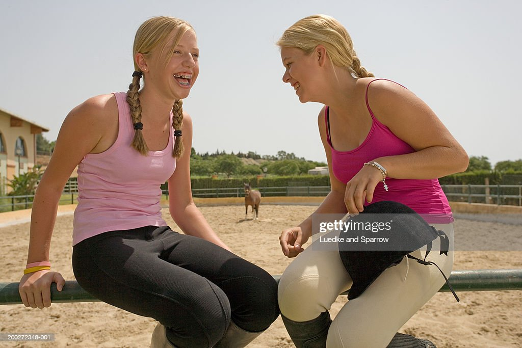Two teenage girls (15-17) sitting on fence laughing : Stock Photo