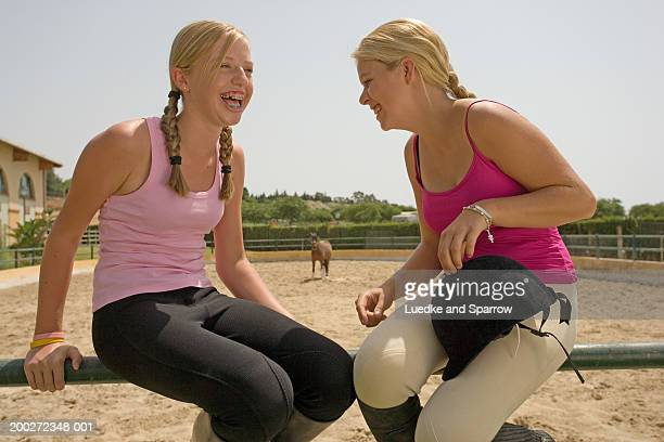 Two teenage girls (15-17) sitting on fence laughing