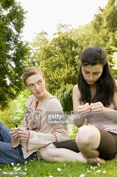 Two teenage girls sitting on lawn, making daisy chains