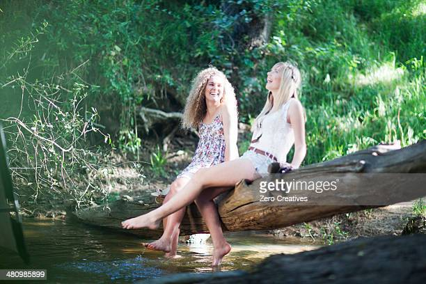 Two teenage girls sitting on tree in woodland stream