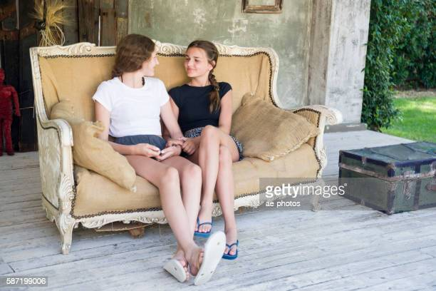Two teenage girls sitting on vintage sofa
