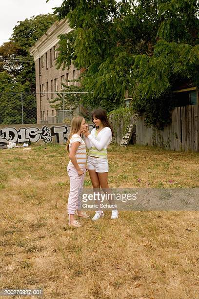 Two teenage girls (12-14) standing in vacant lot, putting on make-up