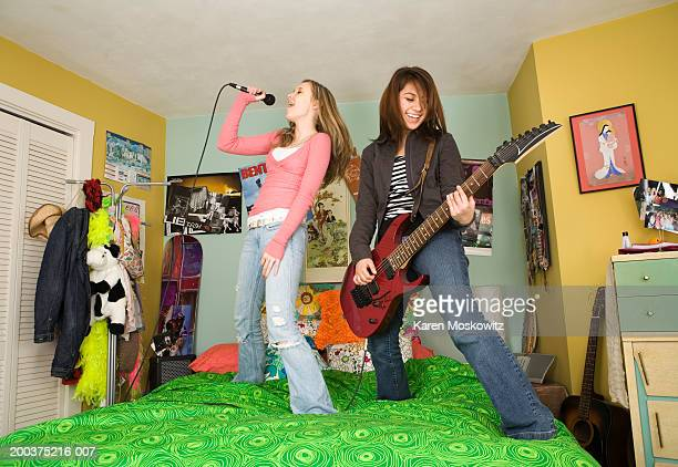 Two teenage girls (14-16) standing on bed, singing and playing guitar
