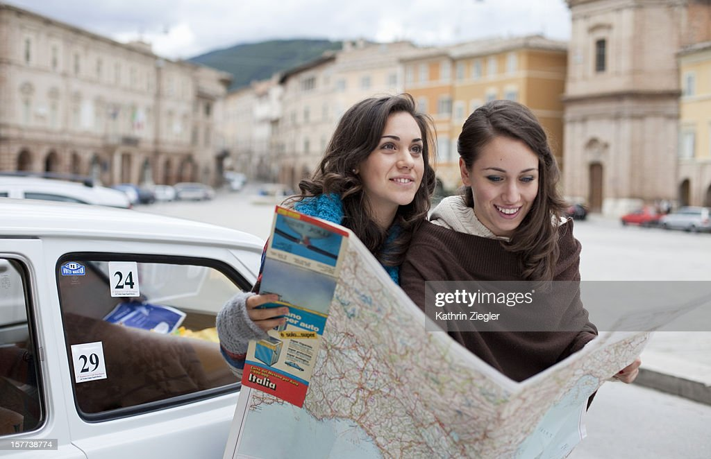 two teenage girls studying map together : Stock Photo