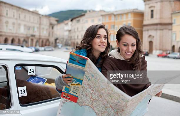 two teenage girls studying map together