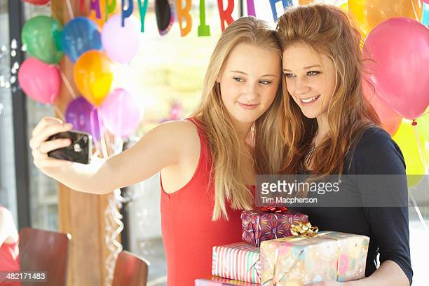Two teenage girls taking selfie at birthday party
